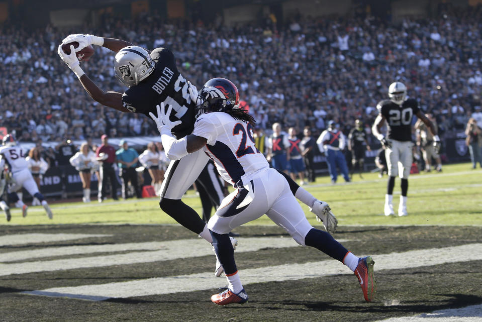 Oakland Raiders wide receiver Brice Butler (12) catches a 5-yard touchdown pass in front of Denver Broncos cornerback Bradley Roby (29) during the second quarter of an NFL football game in Oakland, Calif., Sunday, Nov. 9, 2014. (AP Photo/Marcio Jose Sanchez)