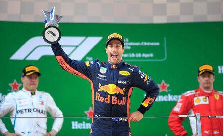FILE PHOTO: Formula One F1 - Chinese Grand Prix - Shanghai International Circuit, Shanghai, China - April 15, 2018 Red Bull's Daniel Ricciardo celebrates with a trophy on the podium after winning the race as Mercedes' Valtteri Bottas and Ferrari's Kimi Raikkonen look on REUTERS/Aly Song