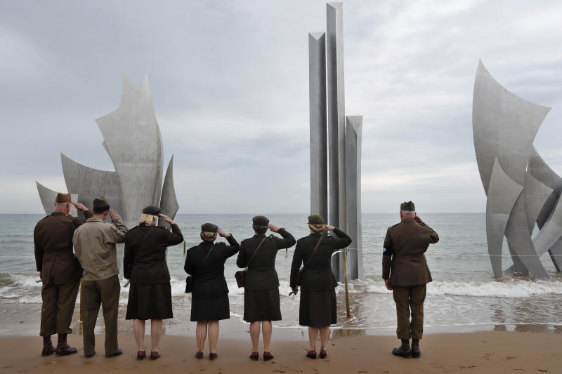 Enthusiasts of England salute in front of The Brave, a monument dedicated to the American soldiers who landed on Omaha Beach on D-Day, in Saint-Laurent-sur-Mer, Tuesday, June 4, 2019, in Normandy. Extensive commemorations are being held in the U.K. and France this week to honor the nearly 160,000 troops from Britain, the United States, Canada and other nations who landed in Normandy on June 6, 1944 in history's biggest amphibious invasion. (AP Photo/Thibault Camus)