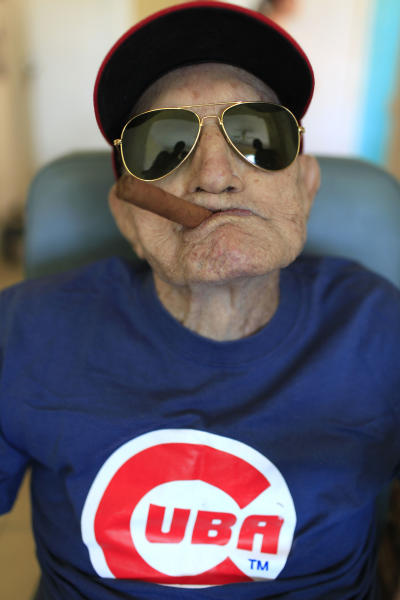"""FILE - In this April 25, 2013 file photo, Conrado Marrero, the world's oldest living former Major League Baseball player, poses for a photo on his 102 birthday at his home in Havana, Cuba. Family members say Marrero has died in Havana. He was 102, just two days short of his 103rd birthday. Grandson Rogelio Marrero confirmed the death on Wednesday, April 23, 2014. Marrero was a diminutive right-hander who went by the nickname """"Connie"""" when he pitched for the Washington Senators in the 1950s. (AP Photo/Franklin Reyes, File)"""