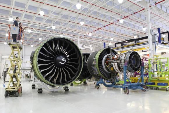Aircraft engines in a manufacturing hangar, with a lift with workers looking at the top of the engines.