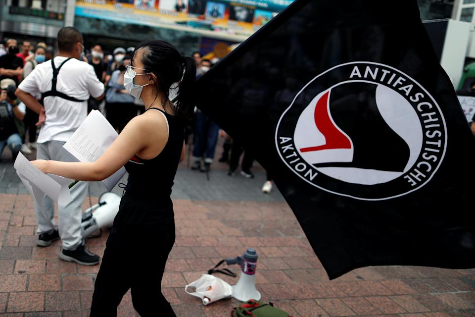 A demonstrator wearing a mask holds an ''Antifaschistische Aktion'' flag during a protest march over the alleged police abuse of a Turkish man, in echoes of a Black Lives Matter protest, following the death of George Floyd who died in police custody in Minneapolis, in Tokyo, Japan June 6, 2020.   REUTERS/Issei Kato