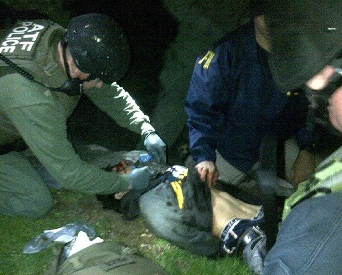 In this Friday, April 19, 2013 photo taken by the Massachusetts State Police, obtained by The Associated Press and authenticated by a member of the Bureau of Alcohol, Tobacco, Firearms and Explosives, ATF and FBI agents check suspect Dzhokhar Tsarnaev for explosives and also give him medical attention after he was apprehended in Watertown, Mass., at the end of a tense day that began with his older brother, Tamerlan, dying in a getaway attempt. Tsarnaev lay hospitalized in serious condition under heavy guard Saturday as investigators continue piecing together the who and why of the two brothers involved in the deadly Boston Marathon bombings. (AP Photo/Massachusetts State Police)