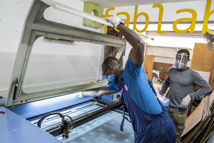 In this photo taken Thursday, April 16, 2020, Mohamed Gueye, center, and Idrissa Sall, right, use a laser cutter to make protective face shields, to be used to protect against transmission of the coronavirus, at the FabLab workshop at the Ker Thiossane multimedia center in Dakar, Senegal. Researchers across Africa are looking for ways to make their own ventilators, protective equipment and hand sanitizers as the continent faces a peak in coronavirus cases long after the United States and European countries have bought up global supplies during the pandemic. (AP Photo/Sylvain Cherkaoui)