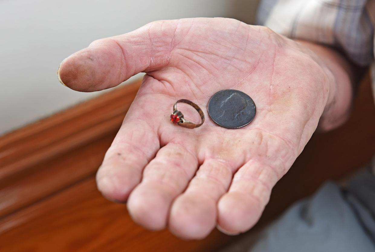CATERS NEWS (PICTURED- A ring and a coin that Colin Steer Has found under his house) - A grandad has spent the last decade digging out a 17ft deep medieval well in his living room after noticing a slight dip in the floor when redecorating. Colin Steer, from Plymouth, discovered the well after he noticed a dip in the floor while redecorating his living room ten years ago and has since spent the last decade digging out the 17ft well. The 70-year-old believes that the well could date back to medieval times after discovering an old sword while digging out the well and plans of the site suggests that the well could date back to the 1500s. Colin said: