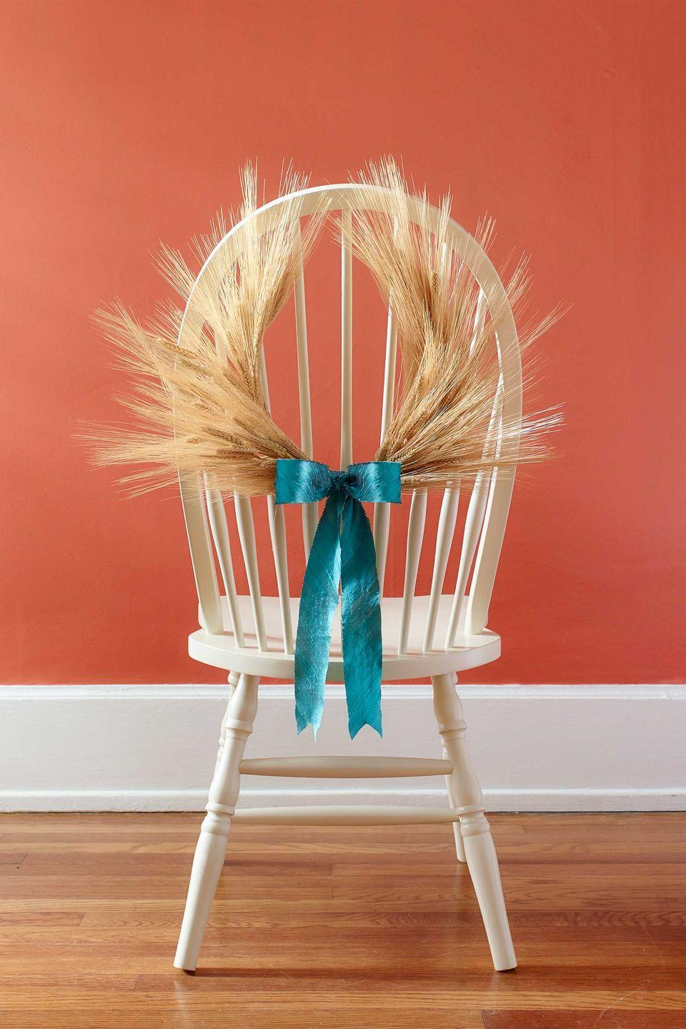 "<p>Spruce up plain chair backs with this seasonal embellishment.</p><p><strong>Step 1: </strong>Cut a 24-inch length of wire and bend it into a horseshoe shape. (We used armature wire, but any wire, including a coat hanger, will work.) Wrap the wire, including any sharp ends, with masking tape.</p><p><strong><strong>Step 2:</strong> </strong>Gather five pieces of dried wheat and trim the stems to 2 ½ inches long. Wrap stems together with <a href=""https://www.amazon.com/DECORA-Gauge-White-Floral-Package/dp/B01A3SBLEW/ref=sr_1_1"" rel=""nofollow noopener"" target=""_blank"" data-ylk=""slk:white, cloth-covered floral wire"" class=""link rapid-noclick-resp"">white, cloth-covered floral wire</a> to make a bundle. Make 9 more bundles of 5 stems each, for a total of 10 bundles.</p><p><strong>Step 3:</strong> Attach the bundles to the horseshoe-shaped wire with floral wire. Place 5 on the right and 5 on the left, leaving a 2-inch space at the center. Tie a bow with 1 yard of ribbon in this space.</p><p><strong><a class=""link rapid-noclick-resp"" href=""https://www.amazon.com/Dried-Triticum-Natural-Wheat-Stalk/dp/B00ZOF9G6A/?tag=syn-yahoo-20&ascsubtag=%5Bartid%7C10050.g.2063%5Bsrc%7Cyahoo-us"" rel=""nofollow noopener"" target=""_blank"" data-ylk=""slk:SHOP DRIED WHEAT"">SHOP DRIED WHEAT</a></strong> </p>"