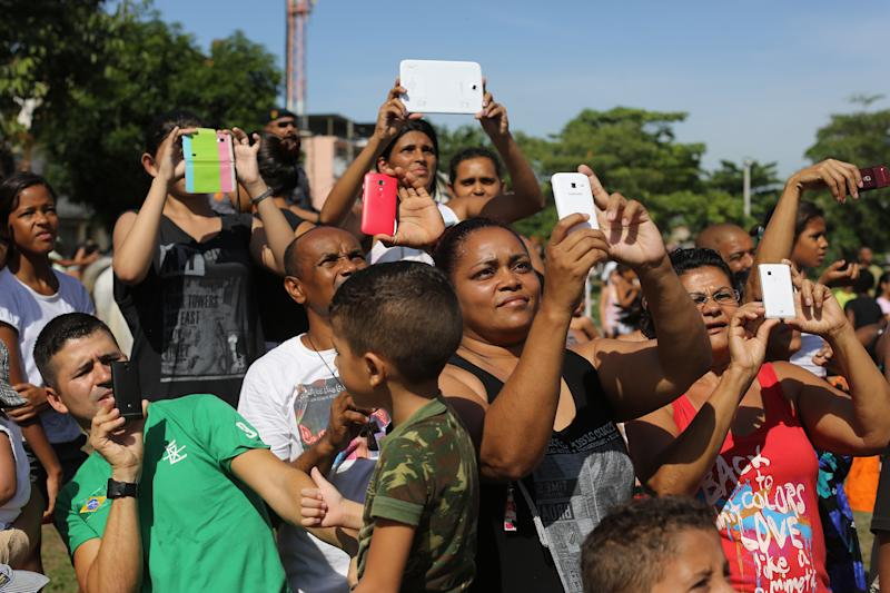 """Residents of Vila Pinheiro slum take photos with their as they watch the flag raising ceremony during a police operation to occupy the Mare slum complex in Rio de Janeiro, Brazil, Sunday, March 30, 2014.ce The Mare complex of slums, home to about 130,000 people and located near the international airport, is the latest area targeted for the government's """"pacification"""" program, which sees officers move in, push out drug gangs and set up permanent police posts. (AP Photo/Leo Correa)"""