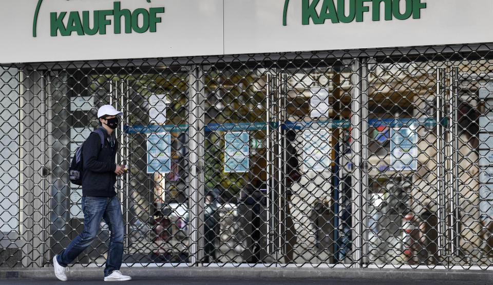 FILE - In this Monday, April 20, 2020 file photo, a man with a face mask to protect against the coronavirus walks past a Galeria Kaufhof warehouse as it is closed in Essen, Germany. German Federal Statistical Office released the preliminary figure for Germany's gross domestic product and said the German economy shrank by 5 percent in the pandemic year 2020. (AP Photo/Martin Meissner, file)