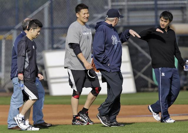 New York Yankees pitcher Masahiro Tanaka, center left of Japan, talks to pitching coach Larry Rothschild, center right, through interpreters during practice at the Yankees' minor league facility Thursday, Feb. 13, 2014, in Tampa, Fla. (AP Photo/Chris O'Meara)