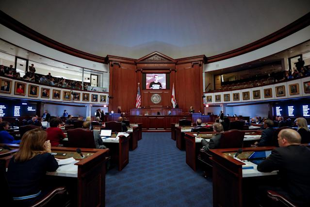 <p>Members of the Florida Senate watch as photos of the victims of Marjory Stoneman Douglas High School mass shooting are projected on the screen in their darkened chamber at the Capitol in Tallahassee, Fla., Feb. 21, 2018. (Photo: Colin Hackley/Reuters) </p>
