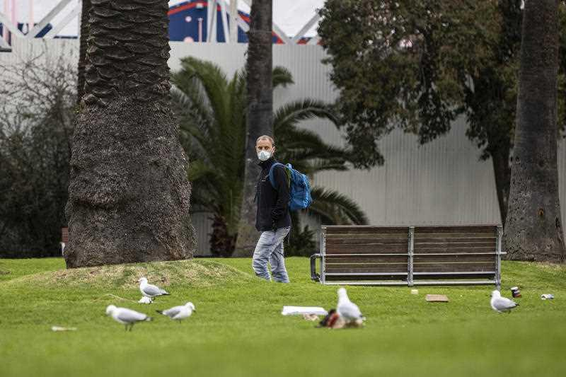 A man is seen walking through the O'Donnell gardens in St Kilda, Melbourne.