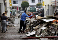 People are cleaning up the damage in Gemuend, Germany, Friday, July 16, 2021 after the flooding of the Urft river. Heavy rains caused mudslides and flooding in the western part of Germany. Multiple have died and dozens are missing as severe flooding in Germany and Belgium turned streams and streets into raging, debris-filled torrents that swept away cars and toppled houses. (Oliver Berg/dpa via AP)