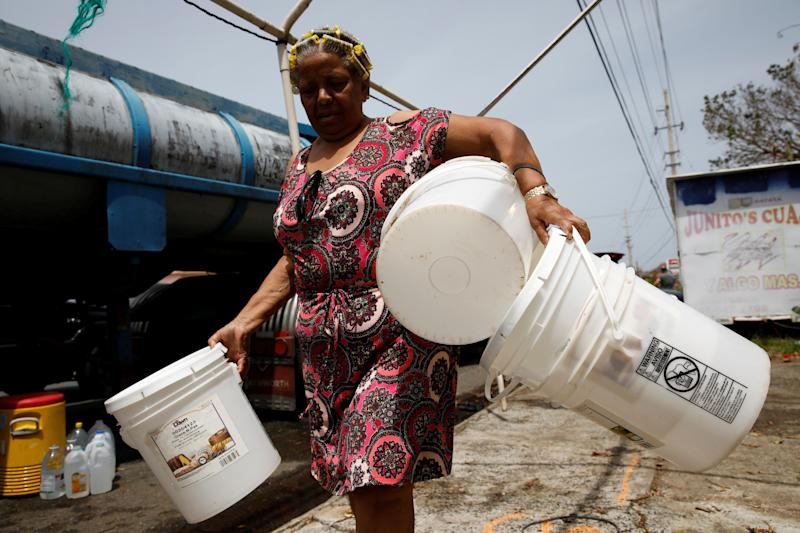 Post-Hurricane Maria, a woman carries buckets to be filled with water from a tank truck in Canovanas, Puerto Rico, on Sept. 26, 2017.