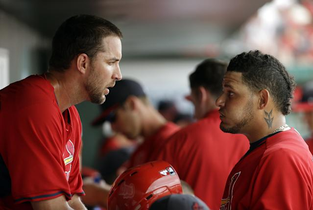 St. Louis Cardinals starting pitcher Adam Wainwright, left, talks with catcher Yadier Molina in the dugout during the eighth inning of an exhibition spring training baseball game against the Washington Nationals, Friday, March 21, 2014, in Jupiter, Fla. (AP Photo/David Goldman)
