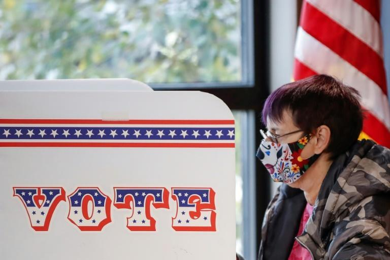 A woman casts her ballot on the first day of in-person early voting for the November 3rd US election in Milwaukee, Wisconsin, on October 20, 2020