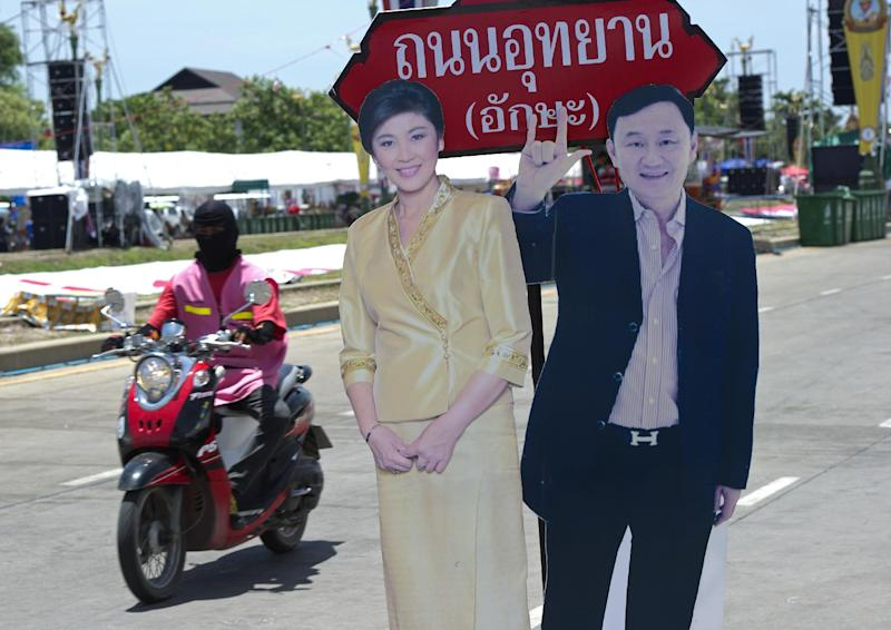 A Thai pro-government 'Red shirts' protester rides past portraits of former Thai prime ministers Yingluck Shinawatra and her brother Thaksin, during a rally on the outskirts of Bangkok, on May 21, 2014 (AFP Photo/Pornchai Kittiwongsakul)