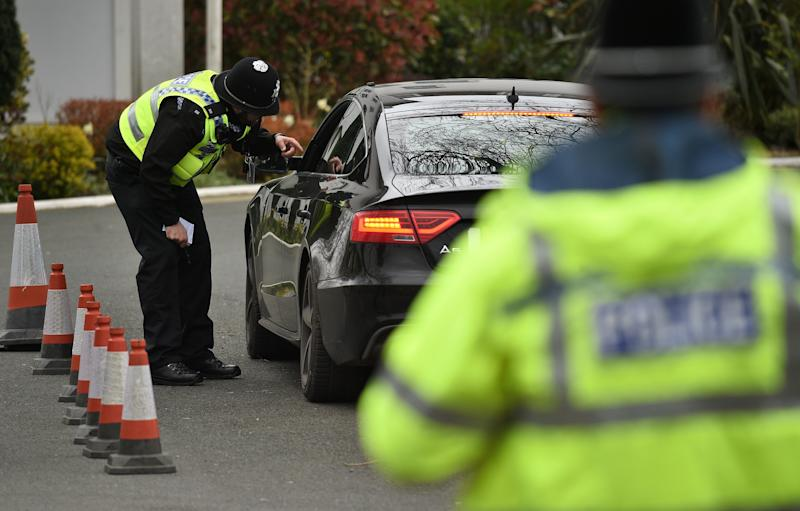 """Police officers from North Yorkshire Police stop motorists in cars to check that their travel is """"essential"""", in line with the British Government's Covid-19 advice to """"Stay at Home"""", in York, northern England on March 30, 2020, as life in Britain continues during the nationwide lockdown to combat the novel coronavirus pandemic. - Life in locked-down Britain may not return to normal for six months or longer as it battles the coronavirus outbreak, a top health official warned on Sunday, as the death toll reached passed 1,200. (Photo by Oli SCARFF / AFP) (Photo by OLI SCARFF/AFP via Getty Images)"""