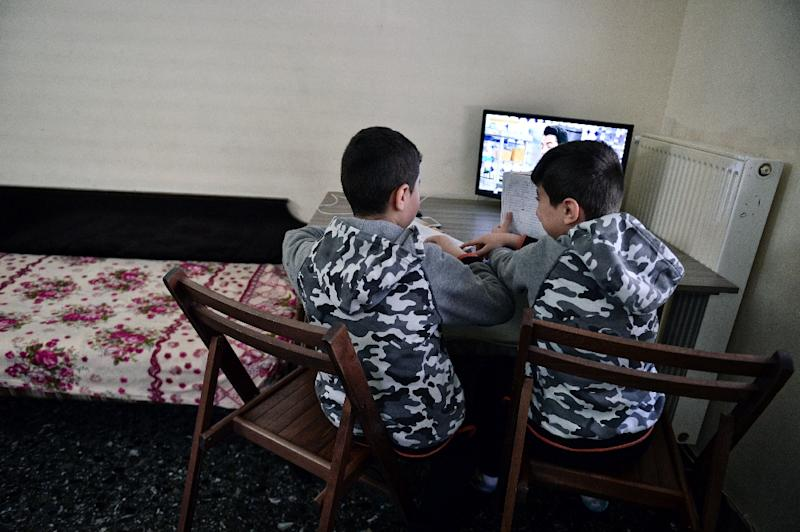 Two young brothers from Syria read their German language homework in an apartment in Athens rented by their family through a refugee housing program (AFP Photo/LOUISA GOULIAMAKI)