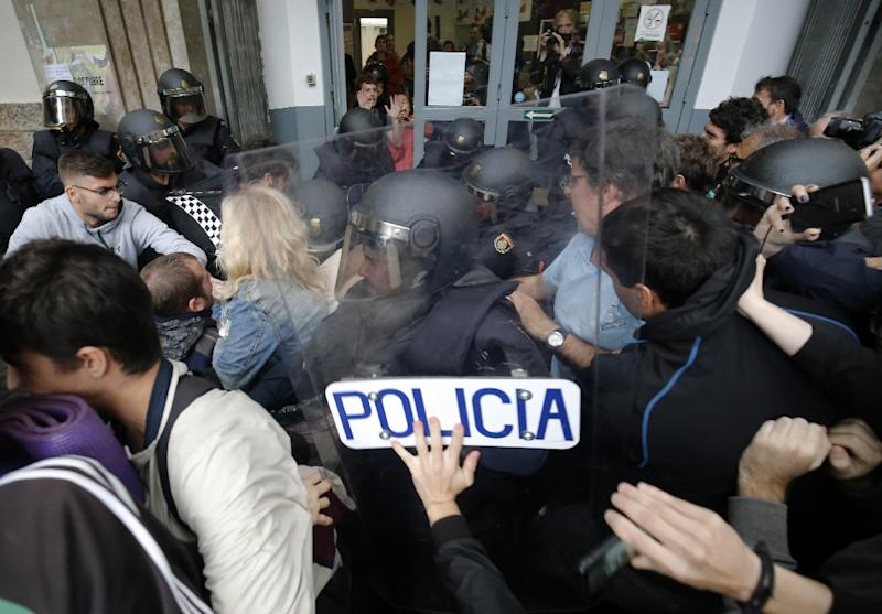 Spanish police officers clash with people outside a polling station in Barcelona on October 1, the day of a referendum on independence for Catalonia banned by Madrid. (AFP Photo/PAU BARRENA)