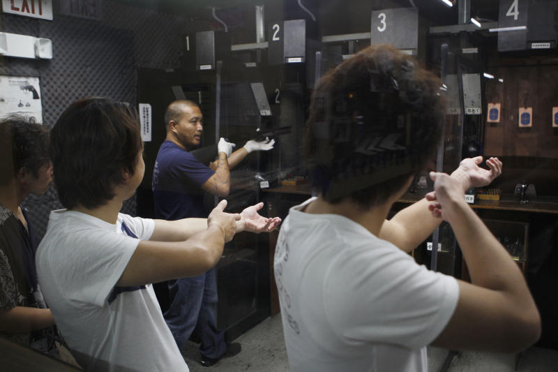 In this photo taken on Saturday, Feb. 2, 2013, Japanese tourists are taught how to fire a rifle at the Western Frontier Village range in Tamuning, Guam. For many tourists from Japan, the biggest thrill is the chance to shoot a gun at one of Guam's ubiquitous ranges, dozens of which are tucked between upscale shopping centers. The U.S. territory of Guam - a tropical island often described as a cheaper version of Hawaii - has long been the perfect place to put guns in the hands of tourists, especially from Japan, where gun ownership is tightly restricted and handguns are banned. Despite a shared sense of shock over the recent rampage by a gunman at America's Sandy Hook Elementary School, the gun tourism business here is as brisk as ever. (AP Photo/Eric Talmadge)