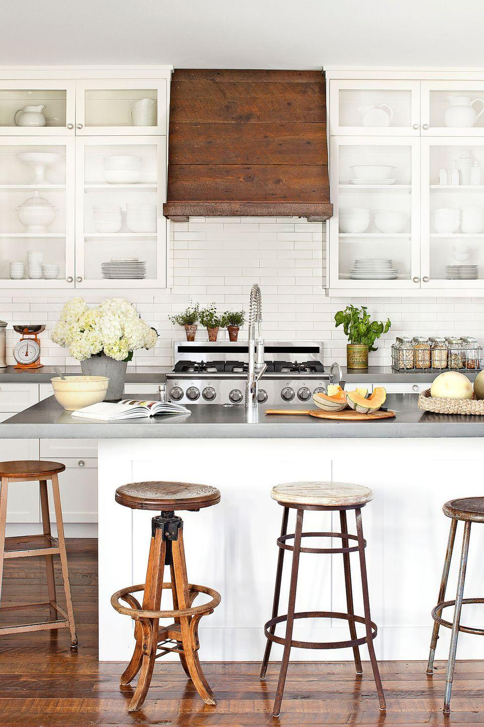 """<p>An assortment of old stools provides quirky charm in the kitchen of this <a href=""""https://www.countryliving.com/home-design/house-tours/g1449/joanna-swanson-budget-home/"""" rel=""""nofollow noopener"""" target=""""_blank"""" data-ylk=""""slk:Oregon farmhouse"""" class=""""link rapid-noclick-resp"""">Oregon farmhouse</a>. Durable concrete countertops from pair with cabinets painted Simple White by Benjamin Moore. Barn wood left over from the floor installation covers a metal Ikea hood.</p>"""