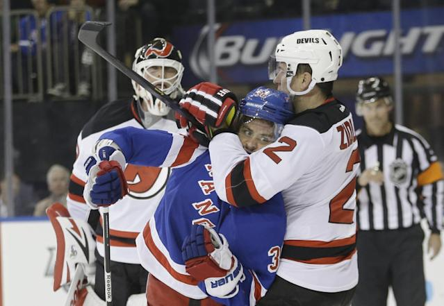 New Jersey Devils' Marek Zidlicky (2) grabs New York Rangers' Mats Zuccarello (36) as Devils goalie Martin Brodeur watches during the second period of an NHL hockey game Tuesday, Nov. 12, 2013, in New York. (AP Photo/Frank Franklin II)