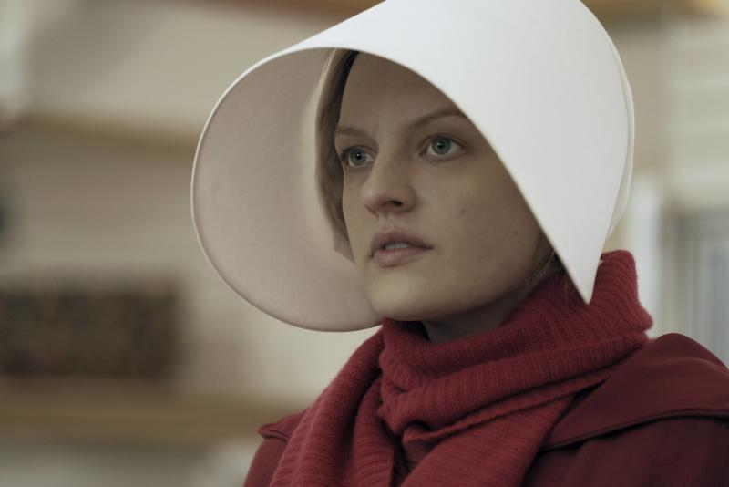 A woman dressed in red, with a long white hood, in a scene from Hulu's