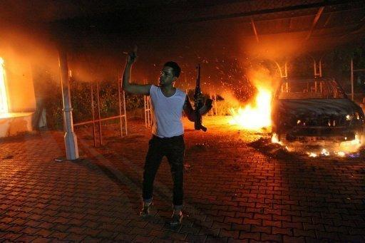 "An armed man waves his rifle as buildings and cars are engulfed in flames after being set on fire inside the US consulate compound in Benghazi on September 11. Mitt Romney on Wednesday hit out at the Obama administration's ""disgraceful"" response to violent protests in Egypt and Libya, accusing it of sympathizing with the Islamist demonstrators"