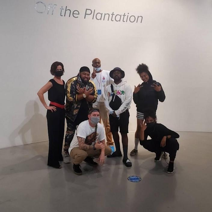 """These are the artists and the gallery owner behind the """"Off the Plantation"""" exhibits at Elder Gallery of Contemporary Art. Standing (L to R) are gallery owner Sonya Pfeiffer and artists Will Jenkins, Benjamin Moore, Dammit Wesley and Carla Aaron-Lopez. Kneeling are artists Kyle Mosher and Kiana Mui."""