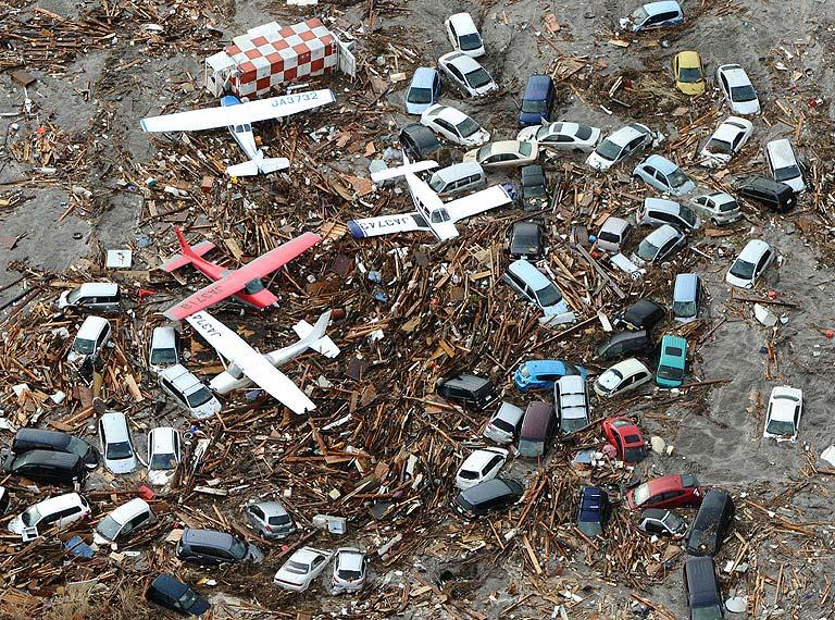 Light planes and vehicles sit among the debris after they were swept by a tsumani that struck Sendai airport in northern Japan.