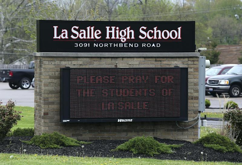 A sign posted in front of La Salle High School, Monday, April 29, 2013, in Cincinnati, asks for prayer after a student pulled out a gun and shot himself in a classroom. La Salle High School west of Cincinnati was locked down until after police arrived and determined there was no threat to other students or staff. A University of Cincinnati Medical Center spokeswoman reported the student's condition as critical Monday afternoon, about six hours after the shooting. (AP Photo/Cincinnati Enquirer, Cara Owsley)