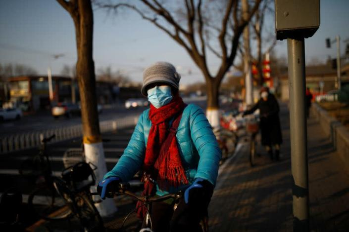 A woman wearing a face mask rides a bicycle as the country is hit by an outbreak of the new coronavirus, in Beijing