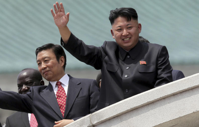North Korea's leader Kim Jong Un, right, is accompanied by Chinese Vice President Li Yuanchao, center, and Ugandan Vice-President Edward Kiwanuka Ssekand as they greet spectators Saturday, July 27, 2013 during the mass military parade celebrating the 60th anniversary of the Korean War armistice in Pyongyang, North Korea. (AP Photo/Wong Maye-E)