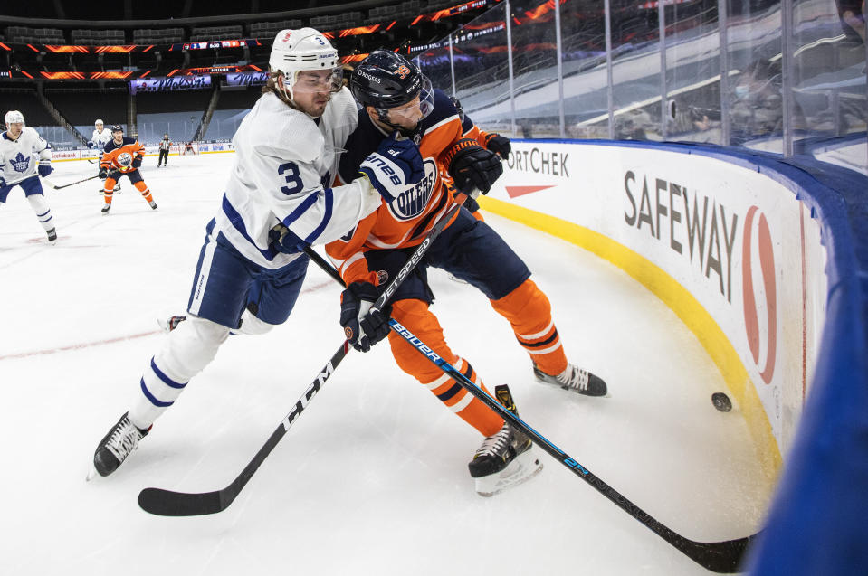 Edmonton Oilers' Alex Chiasson (39) and Toronto Maple Leafs' Justin Holl (3) battle for the puck during the second period of an NHL game in Edmonton, Alberta, on Saturday, Feb. 27, 2021. (Jason Franson/The Canadian Press via AP)
