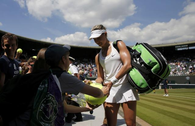 Eugenie Bouchard of Canada signs autographs after defeating Angelique Kerber of Germany in their women's singles quarter-final tennis match at the Wimbledon Tennis Championships, in London July 2, 2014. REUTERS/Suzanne Plunkett (BRITAIN - Tags: SPORT TENNIS)
