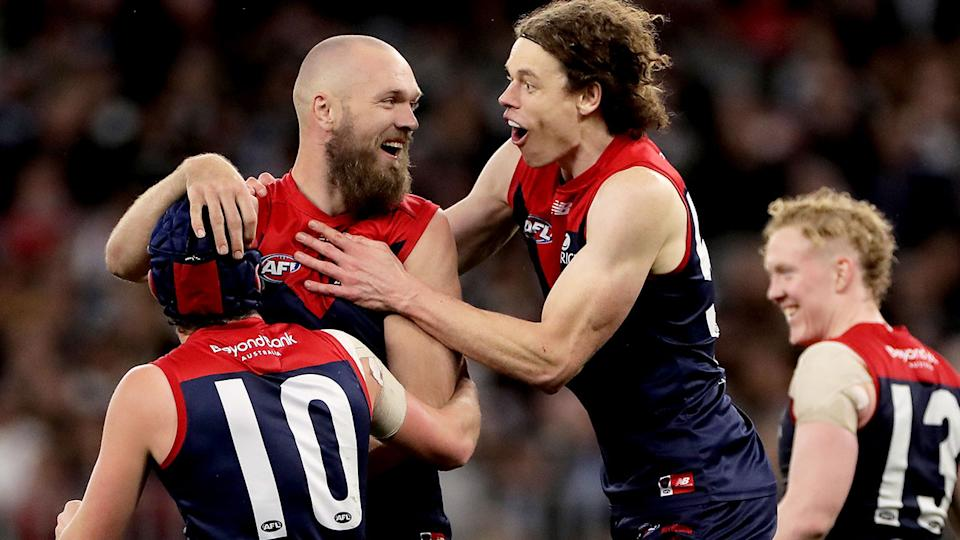 Melbourne Demons players are pictured here reacting to a goal in their preliminary final win.