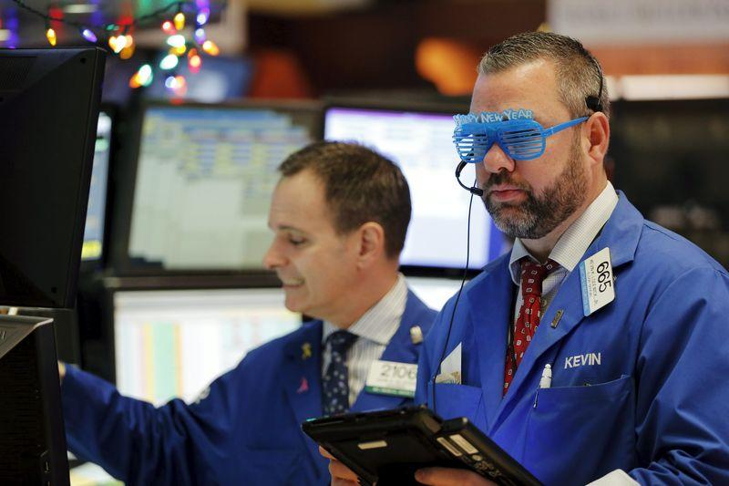 Trader wears plastic glasses to celebrate the last trading day of 2015 while working on the floor of the New York Stock Exchange shortly after the opening bell in New York