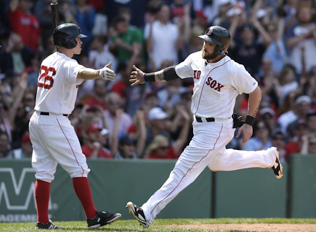Boston Red Sox's Jonny Gomes, right, is welcomed Brock Holt, left, after scoring on a sacrifice fly in the fourth inning of a baseball game against the Tampa Bay Rays, Sunday, June 1, 2014, in Boston. The Red Sox won 4-0. (AP Photo/Steven Senne)