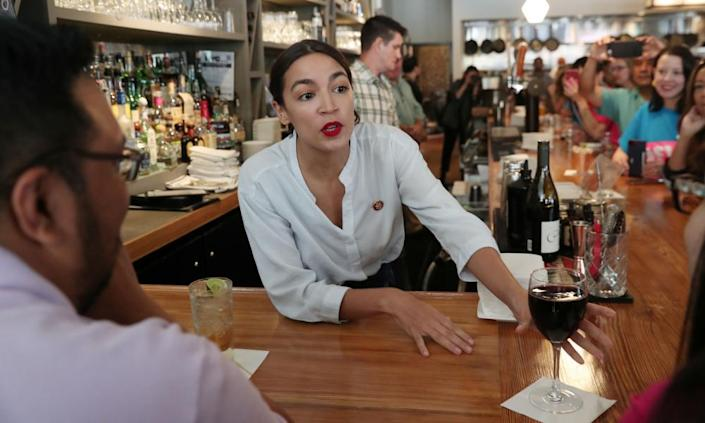 """<span class=""""element-image__caption"""">Alexandria Ocasio-Cortez serves drinks in support of One Fair Wage at the Queensboro restaurant in Queens, New York, on 31 May 2019.</span> <span class=""""element-image__credit"""">Photograph: Shannon Stapleton/Reuters</span>"""