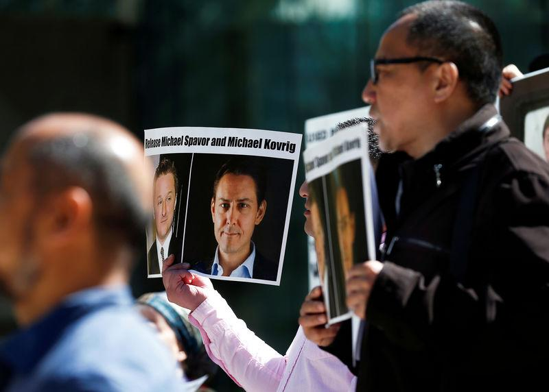 People hold signs calling for China to release Canadian detainees Michael Spavor and Michael Kovrig during a court appearance by Huawei's Financial Chief Meng Wanzhou, outside of British Columbia Supreme Court building in Vancouver, British Col