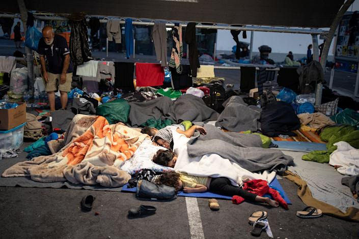 Image: Refugees and migrants from the destroyed Moria camp sleep at the parking space of a supermarket, on the island of Lesbos (ALKIS KONSTANTINIDIS / Reuters)