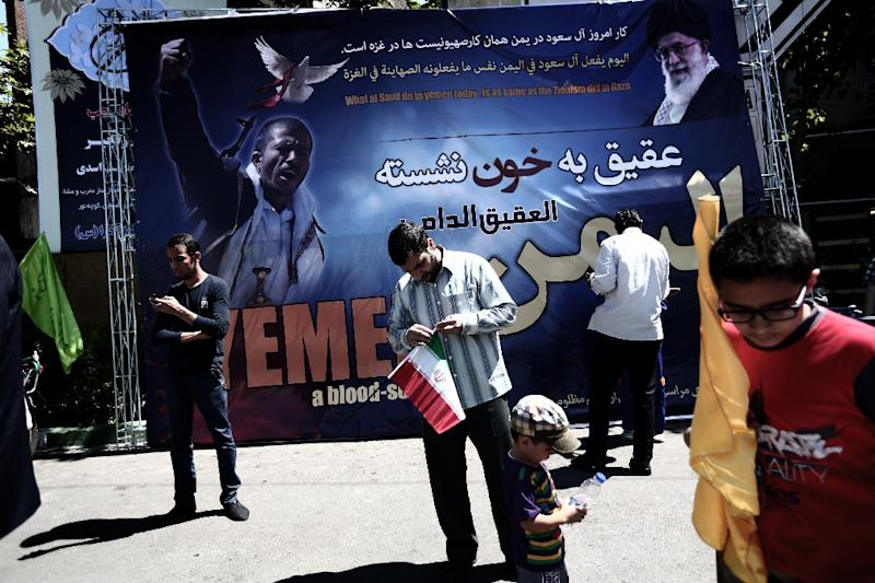 Iranian protesters stand next to a poster bearing portraits of a Yemeni Shiite rebel and Ayatollah Ali Khamenei during a demonstration in Tehran, on May 8, 2015 (AFP Photo/Behrouz Mehri)