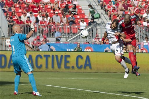 Toronto FC 's Danny Koevermans, right,beats New England Revolution's A.J Soares to head the ball past goalkeeper Matt Reis to score his team's opening goal during first half MLS soccer action in Toronto on Saturday June 23, 2012. (AP Photo/The Canadian Press, Chris Young)
