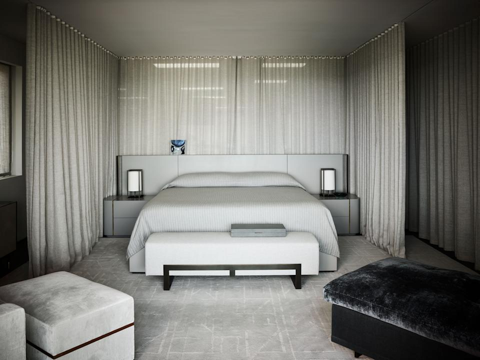 """<div class=""""caption""""> The master bedroom is a study in grays. Since the entire upstairs floor acts as one large suite for Joyner, the <a href=""""https://www.hollyhunt.com/"""" rel=""""nofollow noopener"""" target=""""_blank"""" data-ylk=""""slk:Holly Hunt"""" class=""""link rapid-noclick-resp"""">Holly Hunt</a> curtains around the bed can be open or closed, depending on the level of privacy needed. The bed linens are by <a href=""""https://www.matouk.com/"""" rel=""""nofollow noopener"""" target=""""_blank"""" data-ylk=""""slk:Matouk"""" class=""""link rapid-noclick-resp"""">Matouk</a> and are paired with a custom-made headboard by Wecselman. The gray chair, ottoman, and settee are by Troscan (sourced from Holly Hunt) with an end-of-bed bench by <a href=""""https://ligneatelier.com/"""" rel=""""nofollow noopener"""" target=""""_blank"""" data-ylk=""""slk:Ligne Atelier"""" class=""""link rapid-noclick-resp"""">Ligne Atelier</a>. </div>"""