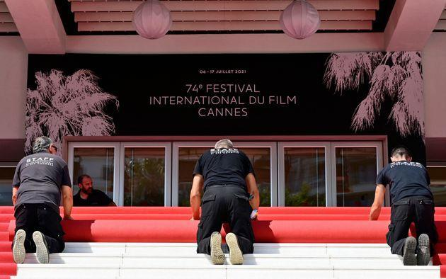 Festival staff roll the red carpet as the 74th edition of the Cannes Film Festival kicks off in southern France, on July 6, 2021. - The famed Cannes Film Festival opens on July 6, and despite social distancing subduing some of its signature glamour, excitement is rife for the first fully fledged film festival since the start of the coronavirus pandemic. (Photo by John MACDOUGALL / AFP) (Photo by JOHN MACDOUGALL/AFP via Getty Images) (Photo: JOHN MACDOUGALL via Getty Images)