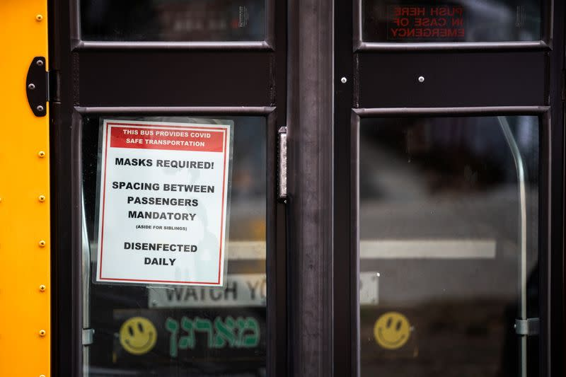 A signage about mask requirement is seen in a window of a school bus during the COVID-19 pandemic in the Brooklyn borough of New York City