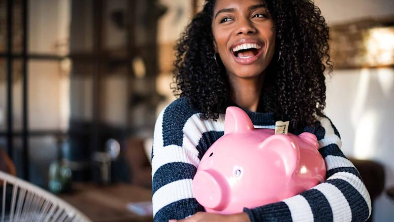 woman holding large pink piggy bank