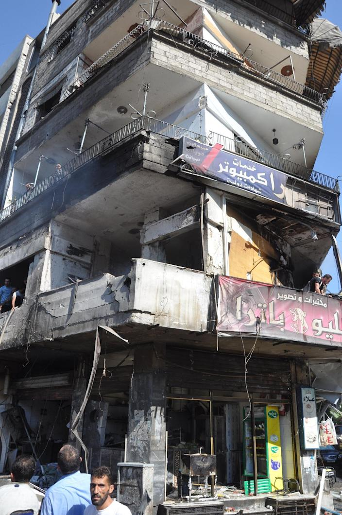 In this photo released by the Syrian official news agency SANA, Syrian citizens look at a damaged building after a car bomb exploded in the suburb of Jaramana, Damascus, Syria, Thursday , July 25, 2013. Syria's state-run news agency says many people have been killed and scores wounded in a powerful car bomb explosion near Damascus. (AP Photo/SANA)