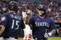 Seattle Mariners' Ty France is congratulated by Kyle Seager after hitting a solo home run during the first inning of a baseball game against the Los Angeles Angels Friday, Sept. 24, 2021, in Anaheim, Calif. (AP Photo/Mark J. Terrill)