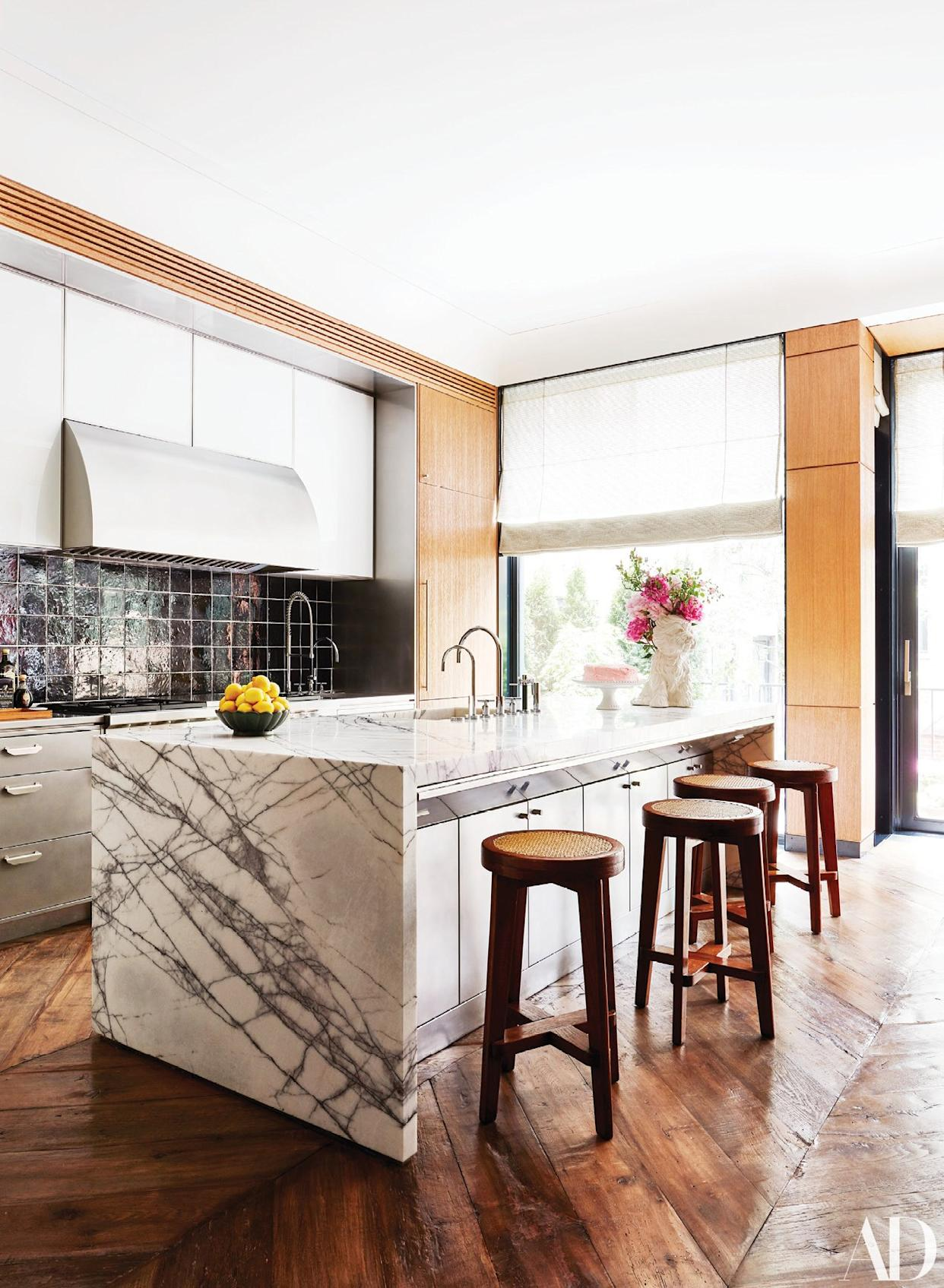 """<div class=""""caption""""> The kitchen features a custom hood and oak millwork by Ingrao. The backsplash is made of tiles by Exquisite surfaces; vintage Pierre Jeanneret stools. </div>"""